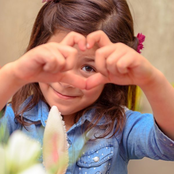 Portrait of a cute little girl making heart, sweet precious child showing love, enjoying traditional spring religious holiday, happy Easter